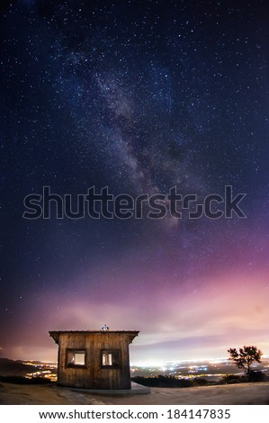 Little house under a magnificent milky way - stock photo