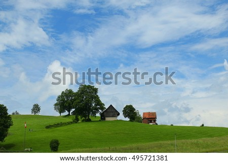 Little houses in green field and blue sky