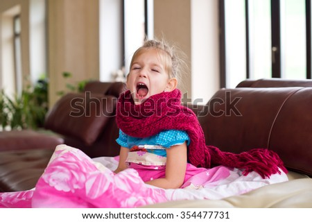 Little ill girl lies in bed with thermometer and scarf on neck getting well of flu - stock photo