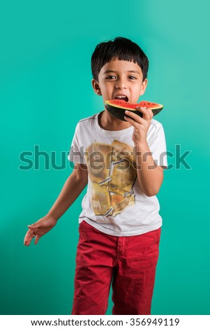 little indian boy eating watermelon isolated on green, asian boy eating watermelon, 4 year old cheerful indian boy eating watermelon, boy with watermelon - stock photo