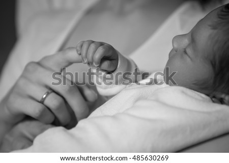 Little infant baby boy sleeping laying on mothers arms and shoulders. Focus on a boy holding mothers finger. Neutral black background, black and white picture. All in white clothes. Happy family