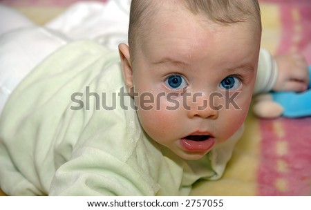 little infant with big blue eyes laying on the stomach