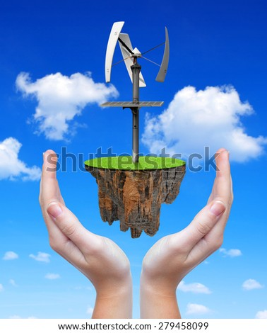 Little island with wind turbine in hands. Alternative energy. - stock photo
