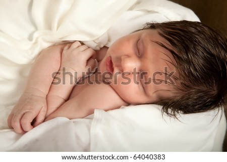 Little Jesus wrapped in swadding clothes in a live christmas nativity scene - stock photo