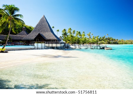 Little jetty and boat on tropical beach with amazing water - stock photo
