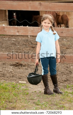 Little jockey - girl on the horse ranch - stock photo