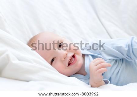 Little joyful baby resting on white bed - stock photo