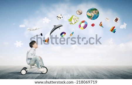 Little joyful cute boy riding tricycle. Elements of this image are furnished by NASA - stock photo