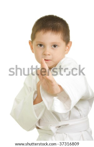 Little karate boy in fighting stand against white background