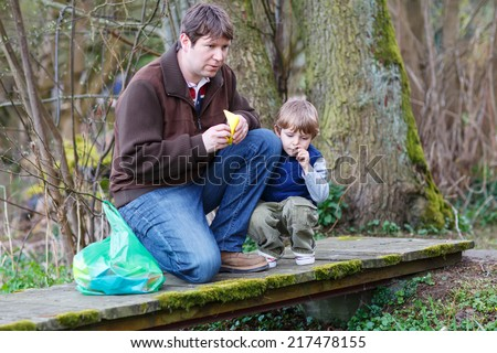 Little kid boy and his dad playing together with colorful paper boats by a river on spring or autumn day. Creative leisure with kids. - stock photo