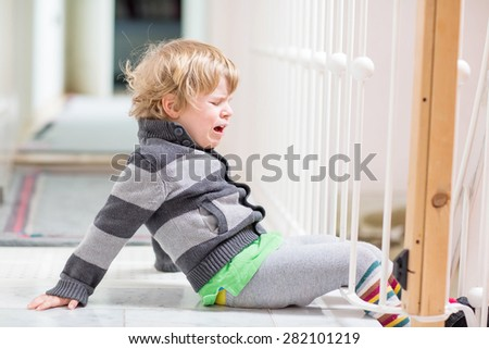 Little kid boy crying at home and showing sad mood, indoors. - stock photo