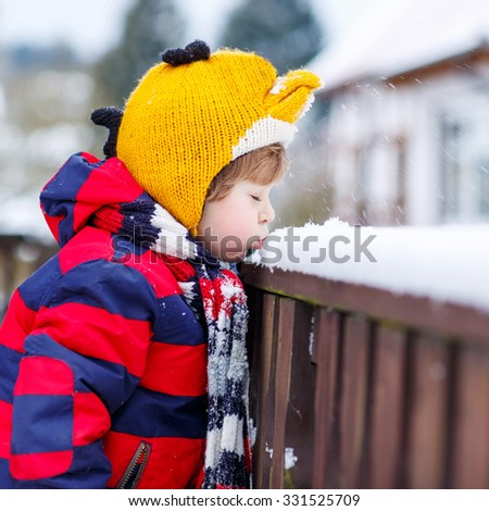 Little kid boy in colorful clothes happy about snow, blowing on it, outdoors  on cold day. Active outdoors leisure with children in winter. - stock photo