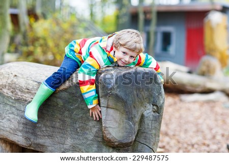 Little kid boy in colorful rain jacket with stripes and gumboots having fun with playing on playground on warm, autumn day, outdoors - stock photo