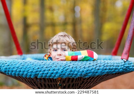 Little kid boy in colorful rain jacket with stripes  having fun with playing chain swing on playground on warm, autumn day, outdoors - stock photo