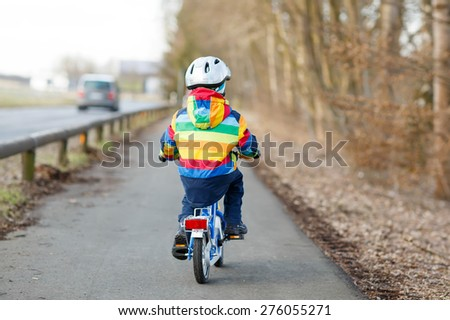 Little kid boy in safety helmet and colorful raincoat riding his first bike and having fun on cold  day, outdoors. From back, street with cars. - stock photo