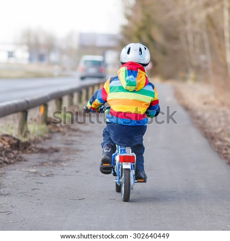 Little kid boy in safety helmet and colorful raincoat riding his first bike and having fun on cold  day, outdoors. From back, street with cars.
