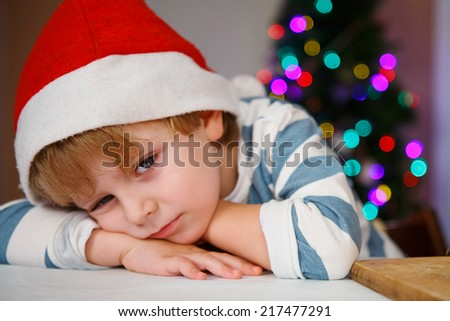 Little kid boy in santa hat with christmas tree and lights on background, dreaming - stock photo