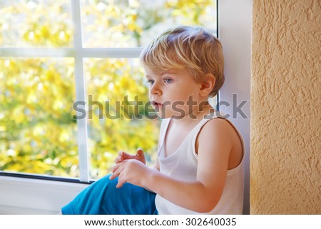 Little kid boy looking out of the window on yellow autumn tree