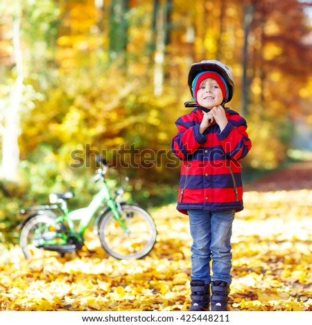 Little kid boy of five years in autumn forest with a bicycle. Active child putting his bike helmet. Safety, sports, leisure with kids concept. - stock photo