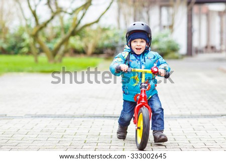 Little kid boy of two years riding with his first bike in the city park. Happy child in colorful clothes. Active leisure for kids outdoors. - stock photo