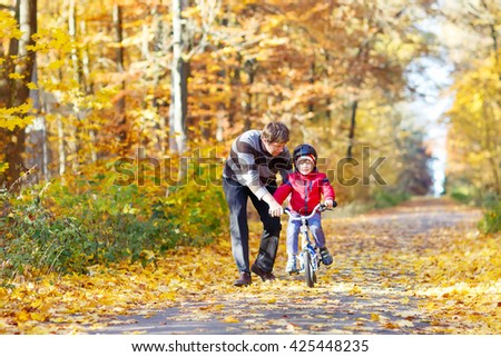 Little kid boy of 3 years and his father in autumn forest with a bicycle. Dad teaching his son. Active family leisure. Child with helmet. Safety, sports, leisure with kids concept. - stock photo