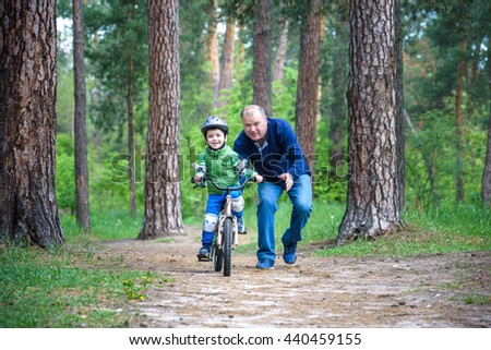 Little kid boy of 4 years and his grand father in summer forest with a bicycle. Grandpa teaching his boy. Man happy about success. Child with helmet. Safety, sports, leisure with kids concept. - stock photo