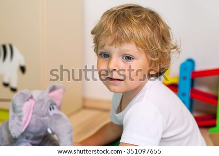 Little kid boy playing with lots of colorful toys indoor. Child having fun in kindergarden or nursery. - stock photo