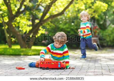 Little kid boy playing with red school bus and toys in summer garden. Another boy on background