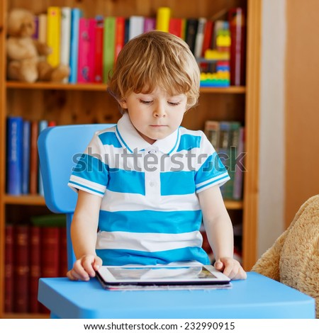 Little kid boy playing with tablet computer in his room at home, indoors. Square format. - stock photo