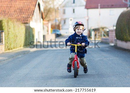 Little kid boy riding bicycle in village or city.