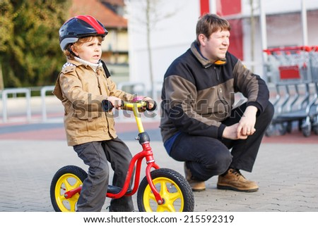 Little kid boy with bicycle and his father in the city. - stock photo