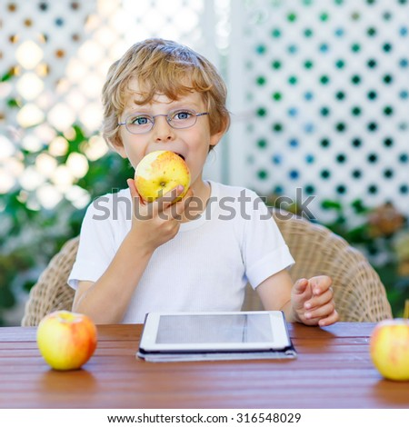 Little kid boy with glasses playing with tablet pc and eating apple. Child making homework for preschool. Lifestyle,school concept. - stock photo