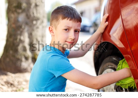Little kid cleaning car wheel, outdoor work - stock photo