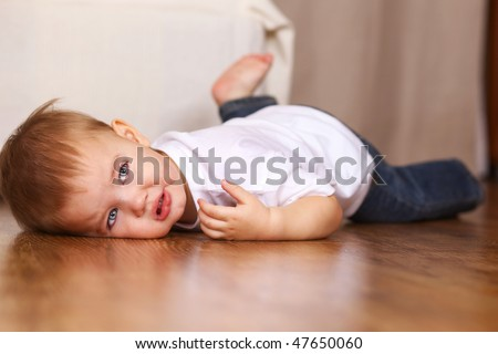 little kid crying lying on floor - stock photo