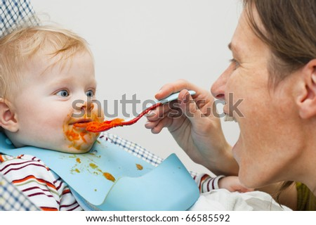 Little kid dirty on his face by the food and mother feeding him