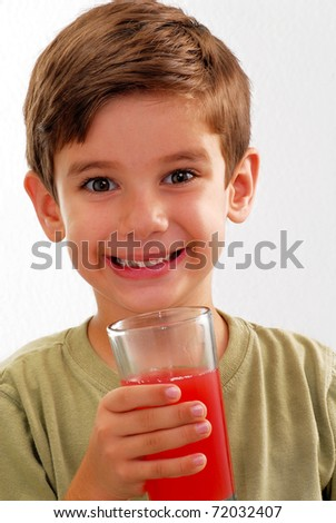 Little kid drinking fruit juice. Little boy holding a juice glass.