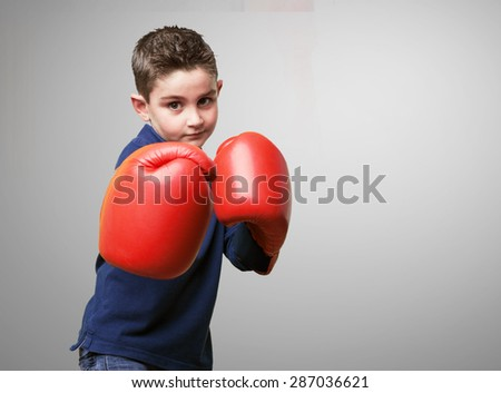 little kid fighting with red boxing gloves - stock photo