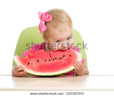 Little kid girl eating watermelon at table isolated on white background - stock photo