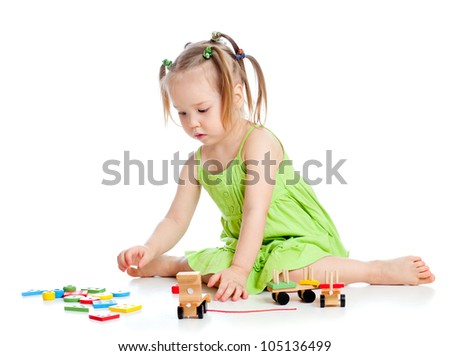 little kid girl playing with colourful toys, isolated over white - stock photo