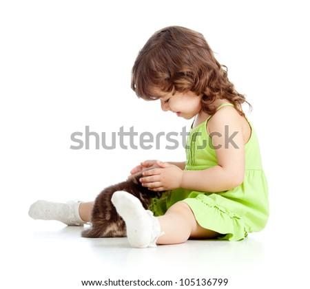 Little kid girl strokes kitten. Isolated on white background - stock photo