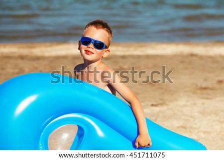 Little kid holding an inflatable mattress on the beach on hot summer day. Smiling boy playing on the beach with air mattress. Child is going to swim in the sea with swimming mattress. Summer vacation - stock photo
