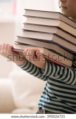 Little kid in a striped shirt holding a pile of books. Education and knowledge concept. Reading children. Back to school.  Schoolboy at the library. - stock photo
