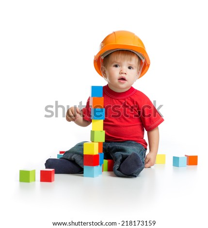 little kid in hard hat with building blocks - stock photo