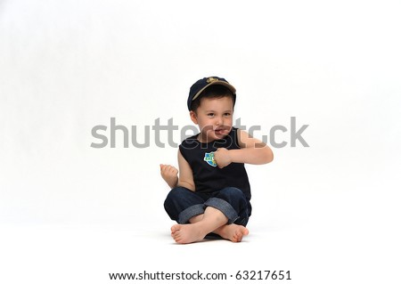 Little kid in navy blue outfit sitting legs crossed waving his arms against white background