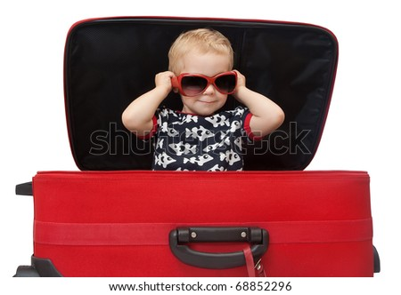 Little kid in sunglasses looking out red suitcase. Isolated on white background