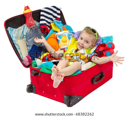 Little kid in travel red suitcase. Packed for vacation in sea resort. Personal belongings: hat, cream, towel. Isolated on white - stock photo