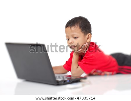 Little kid is playing with laptop while surfing through wireless broadband. - stock photo