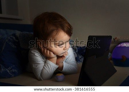Little kid is watching cartoon on a tablet while lying on the bed. Child in white blouse in unlit room lying under the blanket. Child's face is illuminated only bu tablet's screen. - stock photo