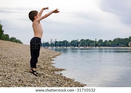 Little kid jumping next to coast of big lake. - stock photo