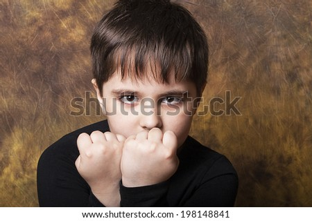 Little kid of seven, ready to fight, studio shot, - stock photo